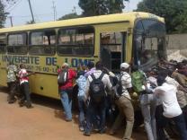 Des étudiants poussant un bus universitaire en panne
